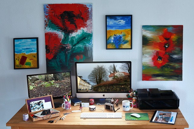 pracovní stůl, kde je technika, počítač, fotoaparát, tiskárna, obrázky a obrazy